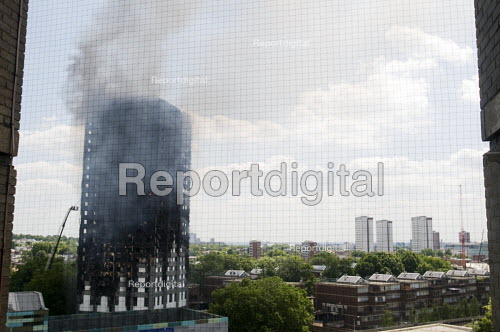 Grenfell Tower Fire. Pockets of fire still visible in some flats as smoke is seen still smouldering a full 12 hours after the raging inferno that engulfed the West London tower block seen on the left resulting in the loss of many lives - Stefano Cagnoni - 2017-06-14