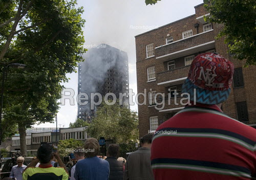 Grenfell Tower Fire. Local residents look on as smoke can be seen still smouldering a full 12 hours after the raging inferno that engulfed the West London tower block seen on the left resulting in the loss of many lives - Stefano Cagnoni - 2017-06-14