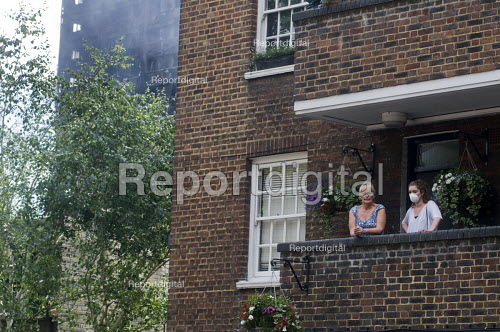 Grenfell Tower Fire. Local residents on their balcony one wearing a mask to filter fumes from the smoke still smouldering a full 12 hours after the raging inferno that engulfed the West London tower block seen very nearby behind the trees to their left - Stefano Cagnoni - 2017-06-14