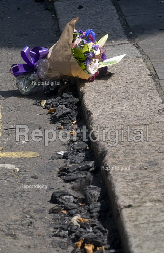 Grenfell Tower Fire. Flowers in memory of the victims laid amongst the ash lying in the gutter that fell from the Grenfell Tower fire that engulfed the West London tower block overnight. The note reads Love and prayers to the victims and families. Justice has to be done - People before money - Stefano Cagnoni - 2017-06-14