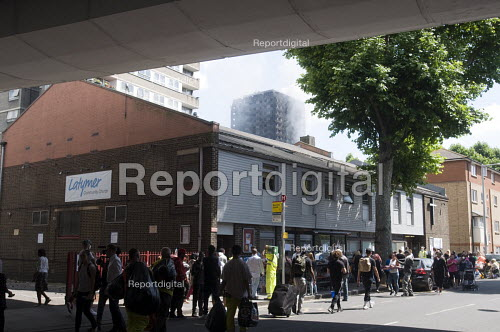 Grenfell Tower Fire. Local residents at the Latymer Community Church Centre in West London just a few hundred metres from Grenfell Tower seen smouldering in the distance bring donations to help victims of the disaster many of whom lost everything they own from their homes in the fire that engulfed the tower block overnight - Stefano Cagnoni - 2017-06-14