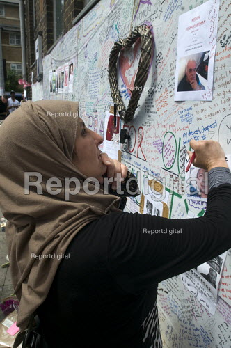 Woman writing a message on the Missing Poster of Hesham Rahman on the Wall of condolence a few hundred metres from the Grenfell Tower fire filled with messages of love and solidarity in memory of the victims of the tragedy, London - Stefano Cagnoni - 2017-06-16