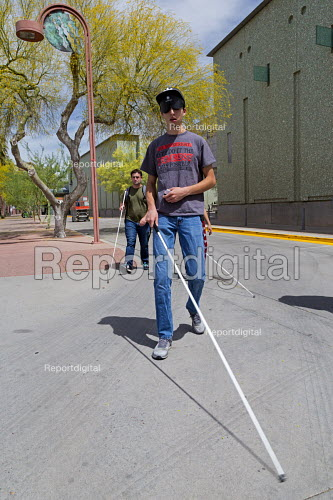 Phoenix, Arizona, USA. Blind and visually impaired young men, some wearing sleep masks, practice navigating city streets with a white cane - Jim West - 2017-04-07
