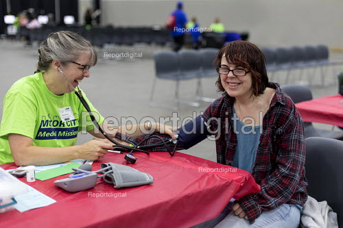 Detroit, Michigan, USA A volunteer nurse taking the blood pressure of a patient, Motor City Medical Mission, a free three day medical clinic sponsored by the Adventist Medical Evangelism Network - Jim West - 2017-08-09