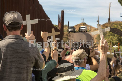 Nogales, Arizona USA Protest on both sides of the USA Mexican border fence for migrants who have died trying to cross the border. US Border Patrol officers watch from the top of the hill. The rally was organized by the School of the Americas Watch, a group of religious and community activists. - Jim West - 2017-11-12