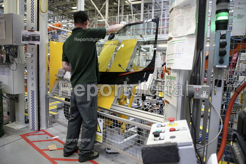 Jaguar Land Rover factory, Solihull. Worker preparing a windscreen for a robot arm to fit to a vehicle - John Harris - 2017-08-21