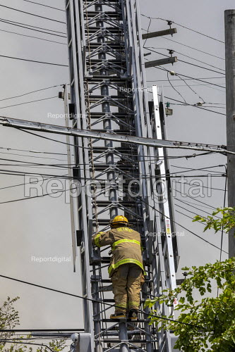 Detroit, Michigan, USA: Frefighter climbing a ladder amid electrical and communications cables, building fire, East side - Jim West - 2018-06-07