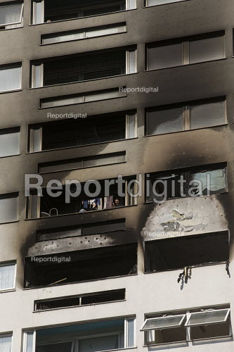 Woman takes down her washing. Grafton House where a twelfth floor fire is contained and brought under control by over 50 firefighters at a 22 story East End Homes tower block in Mile End, East London - Jess Hurd - 2018-06-29