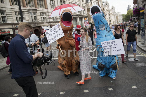 Media with two dinosaurs, Russian TV reporting Together Against Trump marching against the visit to the UK of Donald Trump, London. - Jess Hurd - 2018-07-13