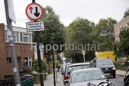 Community activists erecting spoof street signs highlighting the levels of drug dealing in London E2, which apparently has the cheapest heroin in Europe. The anti drugs street art campaign called the Columbia Road Cartel has been commissioned by the Weavers Community Action Group. Shoreditch, East London - Jess Hurd - 2018-09-16
