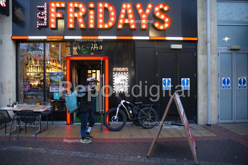 Deliveroo worker, Shopping Centre, Reading, Berkshire. Collecting from TGI Fridays - John Harris - 2018-10-13