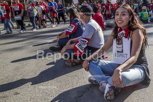 Oakland, California, USA- Hotel workers strike against low pay at the Marriott City Center Hotel sit down blocking the road. Members of Unite Here protest at low wages that force many workers to work an additional job besides their job at the hotel - David Bacon - 2018-10-20