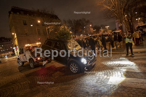 Paris, France protest by Yellow Vest movement, Champs Elysees area. Damaged Mini car with a christmas tree sticking out from the sunroof is towed away - Jess Hurd - 2018-12-08
