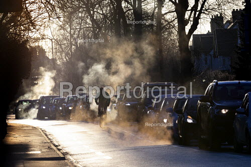 Early morning light catching exhaust emissions. Cycling through traffic congestion, Stratford upon Avon, Warwickshire - John Harris - 2019-01-30