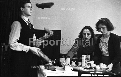 Women clearing the breakfast table as a family of jugglers on tour, 1948, with one juggling bread rolls after breakfast in their lodgings London - Felix H. Man - 1948-04-03