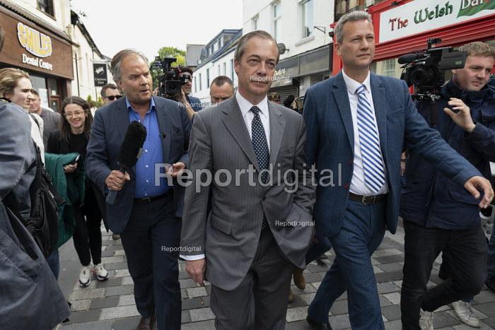 Nigel Farage Brexit Party walking down the High Street pursued by a questioning presenter Matt Frei, Merthyr Tydfil, South Wales, Nathan Gill (R) - John Harris - 2019-05-15