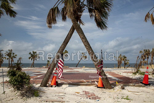 Mexico Beach, Florida, USA: Palm trees and flags where a beach house was destroyed. Destruction from Hurricane Michael 7 months after the storm hit the Florida Panhandle - Jim West - 2019-05-10