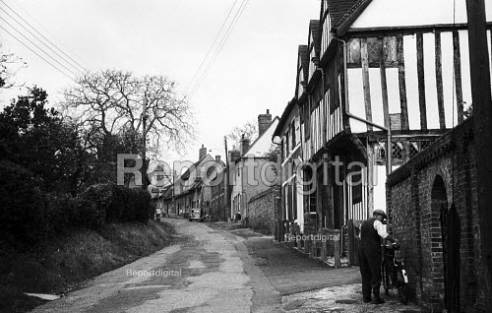 Elderly man parking his bicycle outside his home, mediaeval village of Lavenham Suffolk 1958 - Kurt Hutton - 1958-10-20