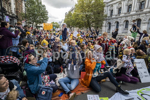 Mothers holding up babies, Extinction Rebellion protest against lack of Government action on climate change. Nonviolent direct action shutting down central London. - Jess Hurd - 2019-10-09