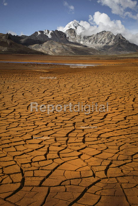The cracked dried up mud of a reservoir which supplies water to the city of La Paz below the Huayna Potosi Mountain. The glaciers in the Andes are retreating, reducing the level to far lower than normal. Run-off from glaciers in the Cordillera Real contributes to reservoirs that supply 1.5 million people in La Paz and the neighboring city El Alto, Bolivia. - Boris Heger - 2009-11-22