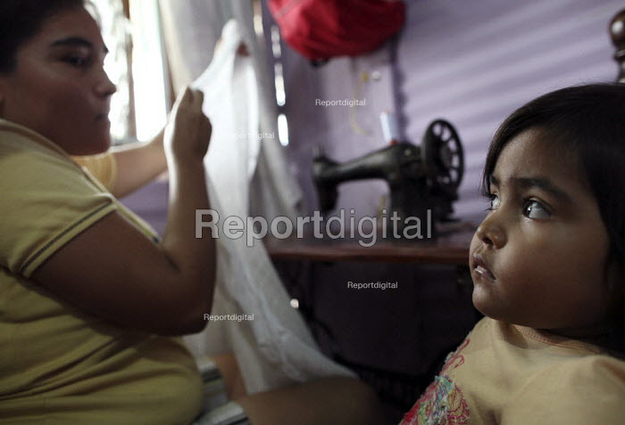 A young colombian refugee watches on as her mother works at home to try to sustain her family. The deteriorating security situation in the regions on the border with Venezuela has led to more than 15000 seeking refuge in the neighbouring country (which has doubled up since 2006). San Cristobal, Venezuela - Boris Heger - 2010-05-27
