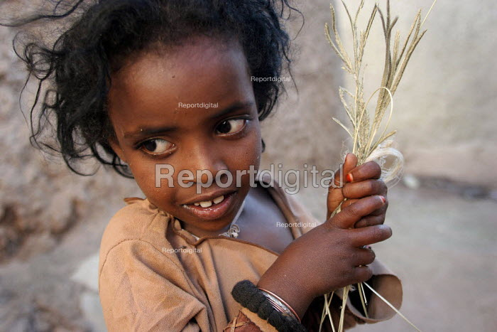 A young girl plays with some grass in the city of Harar, Ethiopia - Boris Heger - 2006-02-05