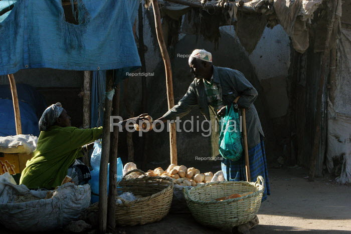 An old man buys some bread in the streets of the city of Harar, Ethiopia - Boris Heger - 2006-02-05