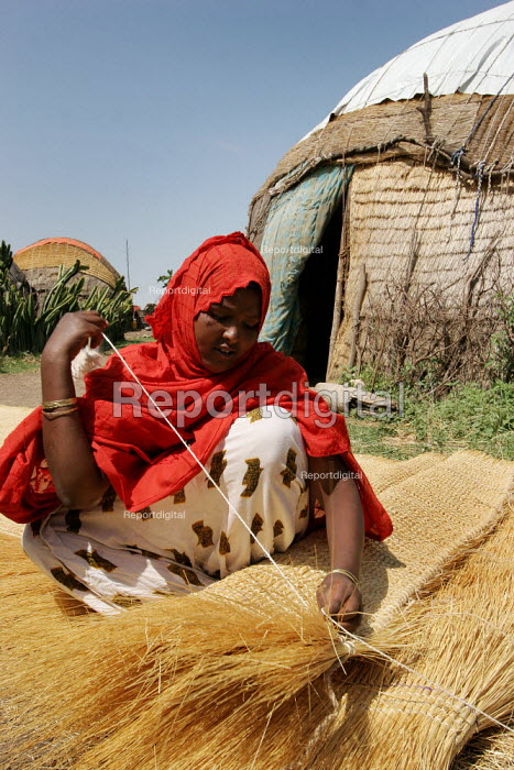 Ferhiya Siad, 16, weaves rush matting in front of her traditional hut in Turwad village, 50 km from Jijiga, Ethiopia - Boris Heger - 2005-08-29