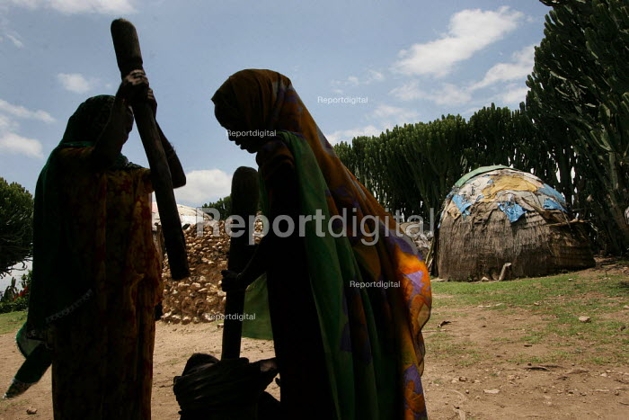 Woman pounding grain with a pestle and mortar in front of traditional somali style huts in the village of Hagadjin, 35 km from Jijiga, Ethiopia, on Sunday, August 28, 2005. - Boris Heger - 2005-08-28