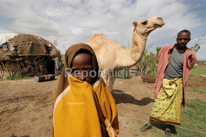 A boy and his father who holds the family camel by a traditional somali hut, in Turwad village, 50 km from Jijiga, Ethiopia, on Monday, August 29, 2005. - Boris Heger - 2005-08-29