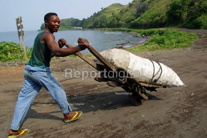 A man carrying goods in a hand made wooden cart pass by the lake Tanganyika, near Goma, Eastern Congo (DRC), May 2004. - Boris Heger - 2004-05-18