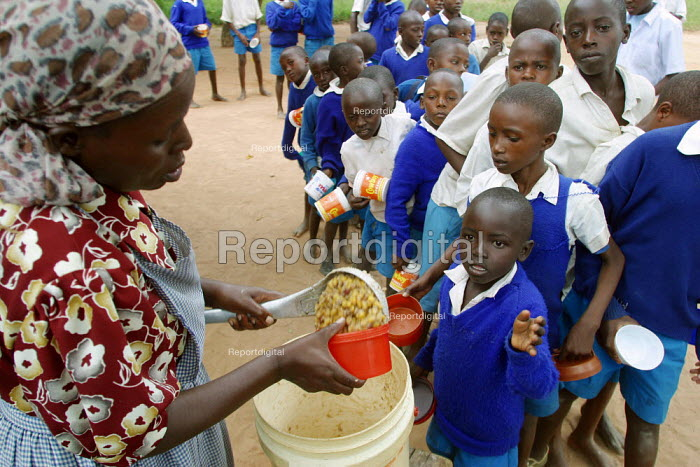A lady distibutes food to pupils, Kajiado school, Machakos rural area, Kenya, May 2004. Without food being given to children, most of them would not attend the classes as they would have to look for feeding themselves by their own means in this poor area. - Boris Heger - 2004-05-11