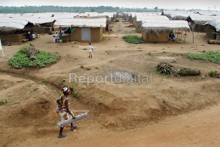 A woman walks on the road in the Blamassee IDP camp, outside of Monrovia, December 2002. - Boris Heger - 2002-12-19