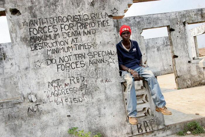 A boy recently returned from refugee camps in Guinea sits on the walls of his former family house destroyed during the war which bears inscription written by the rebels during the war, in Zorzor, near the border with Guinea, Lofa County, Liberia, February 2006. - Boris Heger - 2006-02-23
