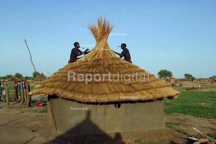 Dinkas people terminate the new rood of their traditional hut, near Padak, South Sudan, April 2004. - Boris Heger - 2004-04-28
