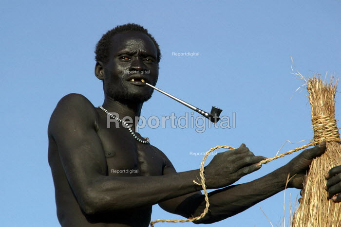 A Dinka terminate the new rood of their traditional hut, near Padak, South Sudan, April 2004. - Boris Heger - 2004-04-28