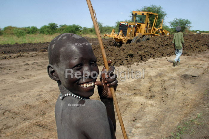 A Dinka boy smiles as heavy machinery prepare a new road, near Padak, South Sudan, April 2004. The road which will be constructed with foreign aid, is meant to develop this very isolated region and develop a new local economy. - Boris Heger - 2004-04-28