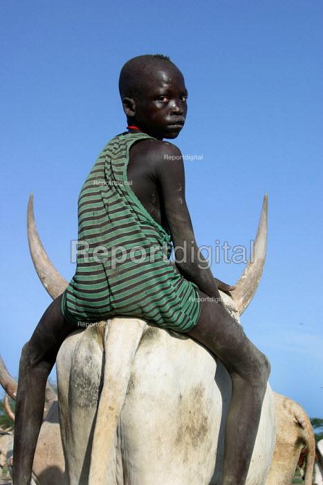 Dinka youth riding on a cow near Padak, South Sudan, Africa 2004 - Boris Heger - 2004-04-28