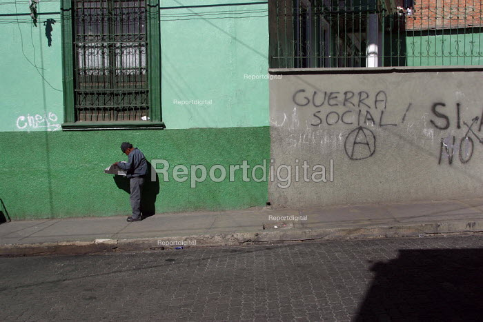 Local in front of a graffiti reading social war and the Anarchy symbol, in the citys center, La Paz, Bolivia, August 2004 - Boris Heger - 2006-08-29