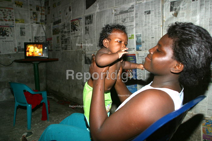 Mother and child displaced in front of the television in their shelter, in Quibdo, Choco region, Colombia, February 2004. There are an estimated 3 million people displaced by conflict with guerrilla groups. - Boris Heger - 2006-08-20