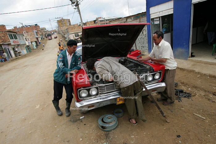 People repair an old car in Los Altos de Cazuca, one of the worst slums in Bogota, Colombia, January 2006. There are an estimated 3 million people displaced by conflict with guerrilla groups. - Boris Heger - 2006-08-30