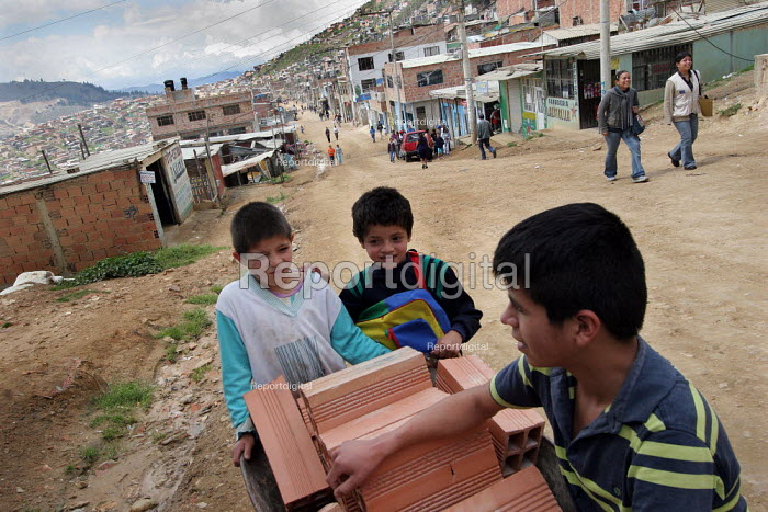 Children work carrying construction material in the streets of Los Altos de Cazuca, one of the worst slums in Bogota, Colombia, January 2006. There are an estimated 3 million people displaced by conflict with guerrilla groups. - Boris Heger - 2006-08-30