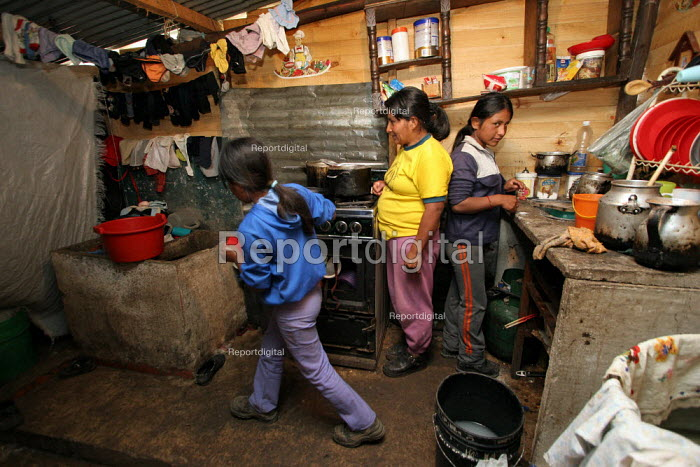 A displaced woman and her sons cook in their shelter, in Los Altos de Cazuca, oone of the worst slums in Bogota, Colombia, January 2006. There are an estimated 3 million people displaced by conflict with guerrilla groups. - Boris Heger - 2006-08-30