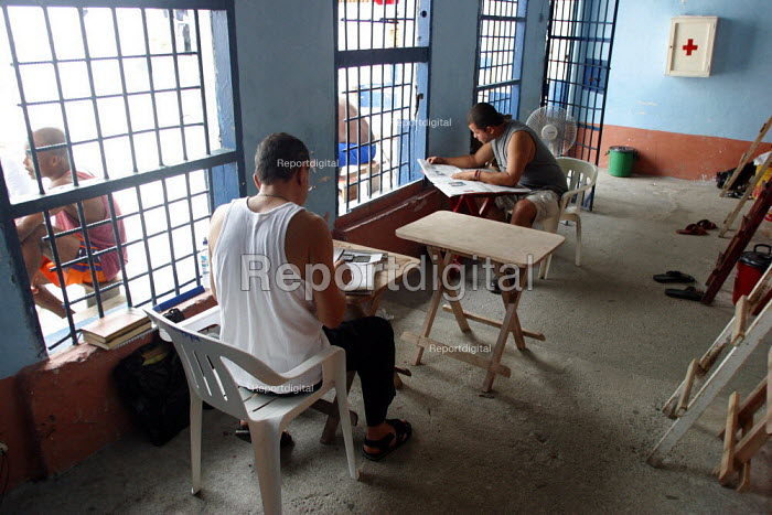 Detainees reading newspapers and writing to relatives, at the central jail, Quibdo, Colombia, August 2004. - Boris Heger - 2006-08-30