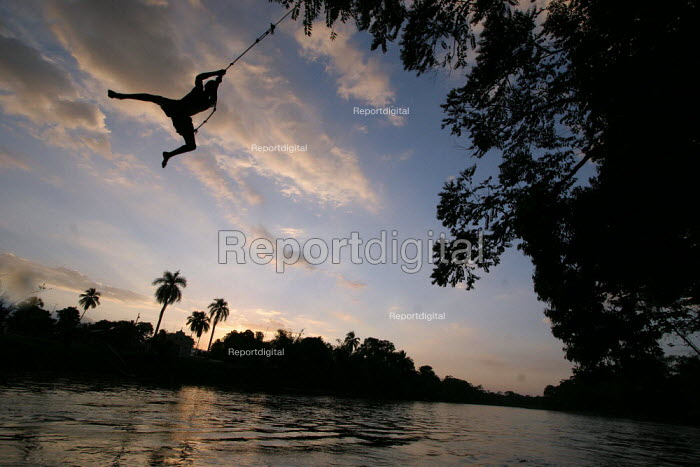 A colombian refugee boy playing with a rope swing from a tree on the riverbank, Boca de Cupe, Darien region, Panama, January 2006. This region is very remote. - Boris Heger - 2006-08-30