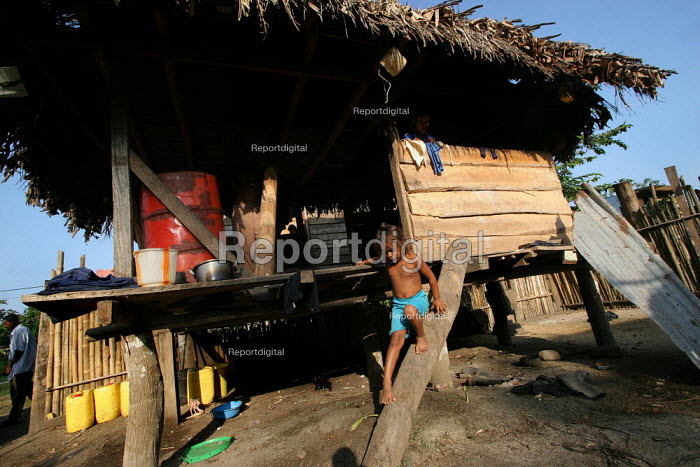 A Colombian refugee boy comes down his hut by a traditional wooden stairs, El Real, Darien region, Panama, January 2006. This region is very remote. - Boris Heger - 2006-08-30