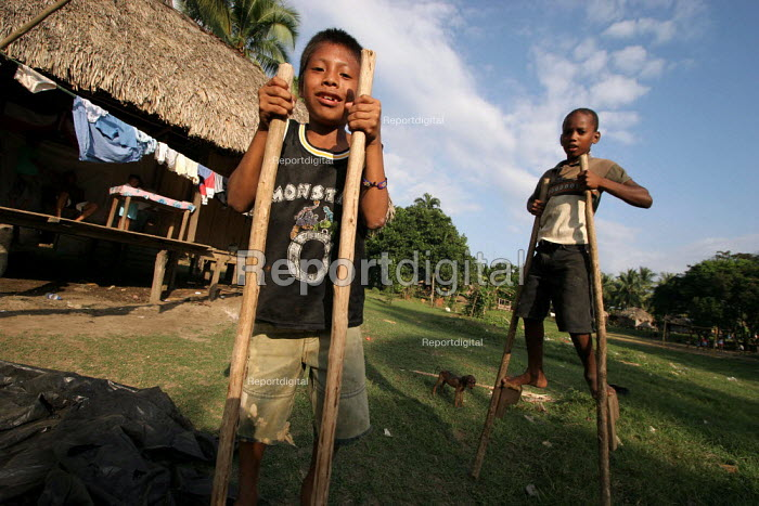 Colombian refugees displaced by the civil war in their country and local children play together walking on stilts, a traditional game in the region, Boca de Cupe, Darien region, Panama, January 2006. Many of the some 12,500 refugees sheltering in Darien region are of indigenous or Afro-Colombian descent.This region is very remote. - Boris Heger - 2006-08-30