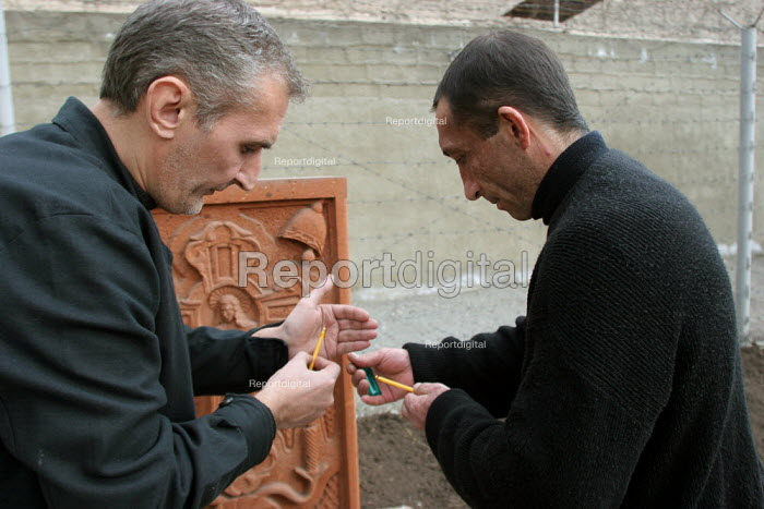Two detainees who have tuberculosis light a candel before praying for their health, at the central prisons hospital, Yerevan, Armenia, February 2005. Tuberculosis is a disease that is widespread in jails of the Caucasus region. - Boris Heger - 2005-02-28