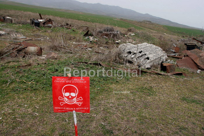 Mine danger sign on a former front line where deminers are set to start working, near Khramort, Nagorno Karabakh, Azerbaidjan, March 2005. The region, although officially located within Azerbaidjan, is being occupied by Armenia and has became a de facto Republic strongly linked with Armenia. The conflict, considered is still pending and the status of Nagorno Karabakh is unresolved. - Boris Heger - 2005-03-03