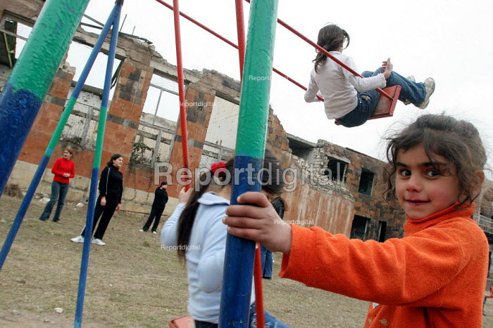 Children play in front of their former school destroyed during the war, Khramort, Nagorno Karabakh, Azerbaidjan, March 2005. The region, although officially located within Azerbaidjan, is being occupied by Armenia and has became a de facto Republic strongly linked with Armenia. The conflict, considered is still pending and the status of Nagorno Karabakh is unresolved. - Boris Heger - 2005-03-03